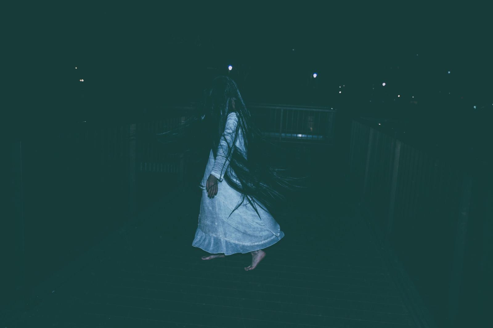 「真夜中に髪の毛を振り乱す女性」の写真[モデル:緋真煉]