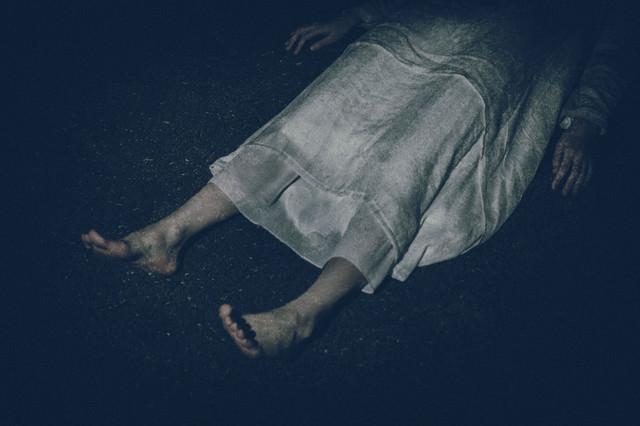 横たわる白いワンピースを着た女性の足元の写真