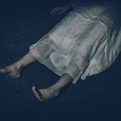 「横たわる白いワンピースを着た女性の足元」の写真素材