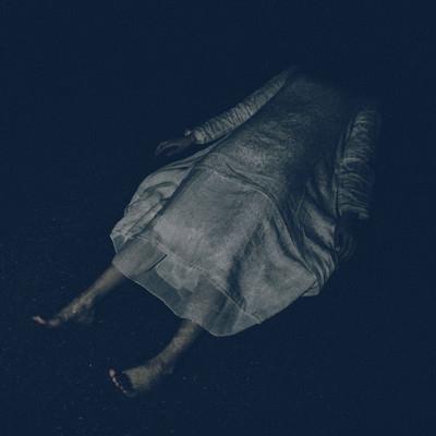 「白いワンピースを着て横たわる女性」の写真素材