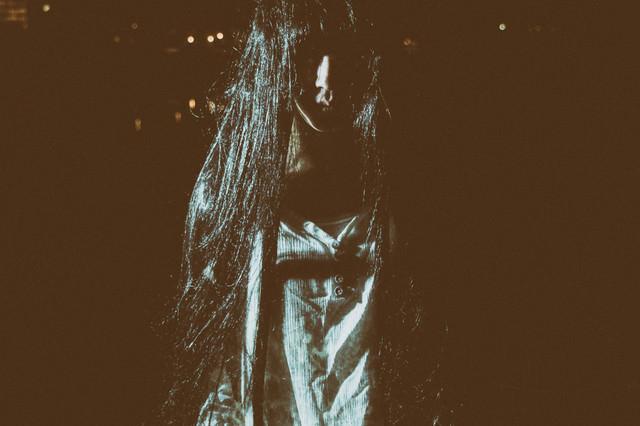 暗闇の中からずっとこちらを見つめる女性の写真