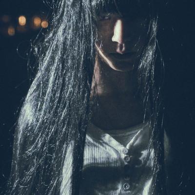 伸びた髪の間から怨めしそうに見つめる女性の写真