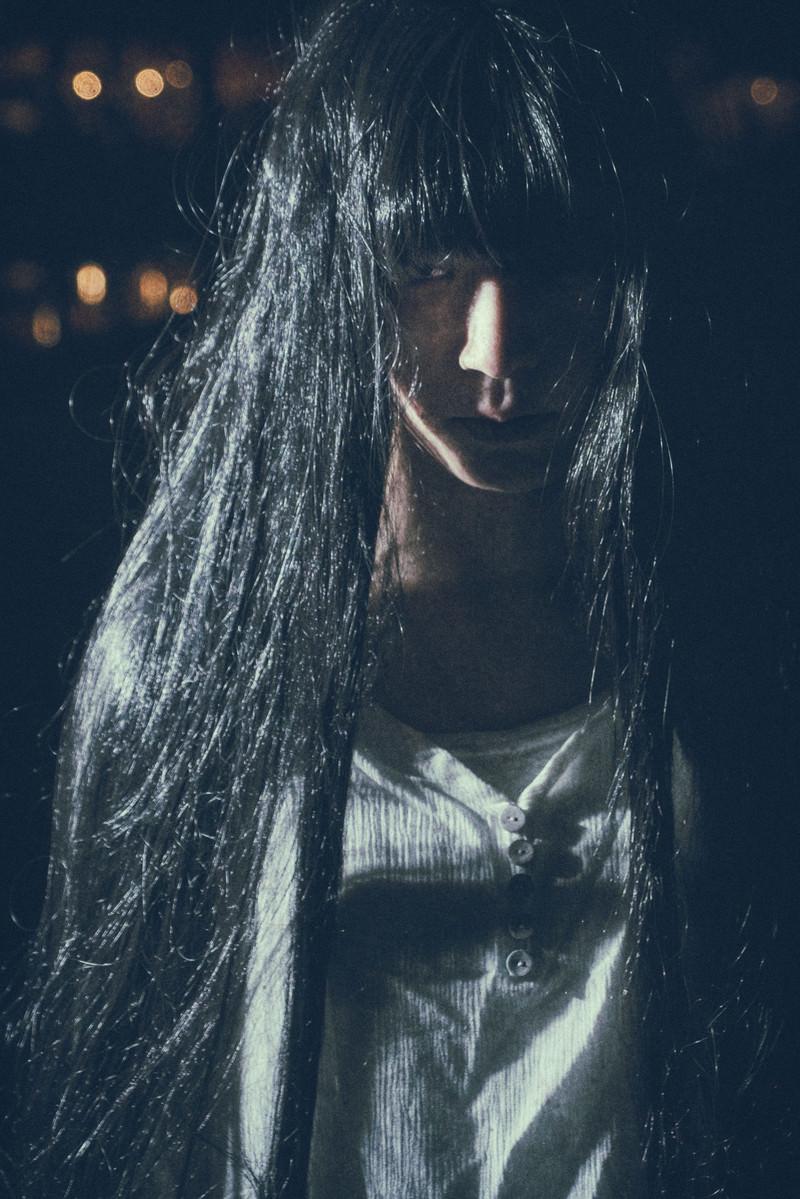 「伸びた髪の間から怨めしそうに見つめる女性」の写真[モデル:緋真煉]