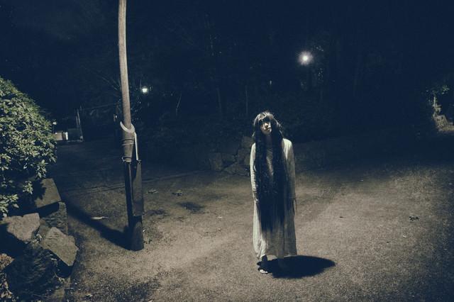真夜中の公園の照明の下で仁王立ちする女性の写真