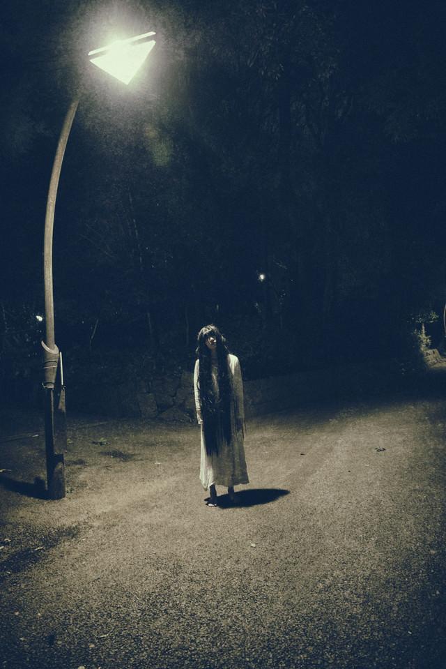 真夜中の公園を徘徊する裸足の女性の写真
