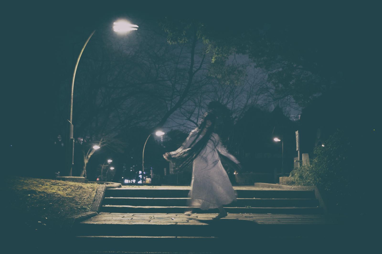 「深夜の公園で不気味な動きをする女性」の写真[モデル:緋真煉]