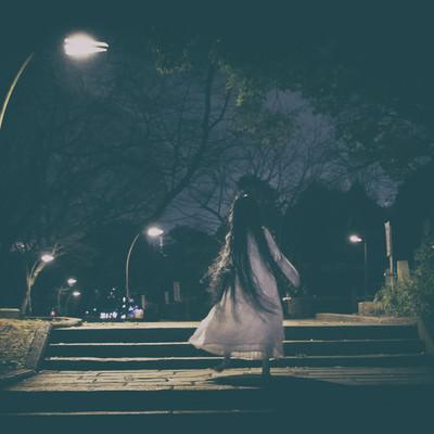 「真夜中の公園をスキップで徘徊する女性」の写真素材