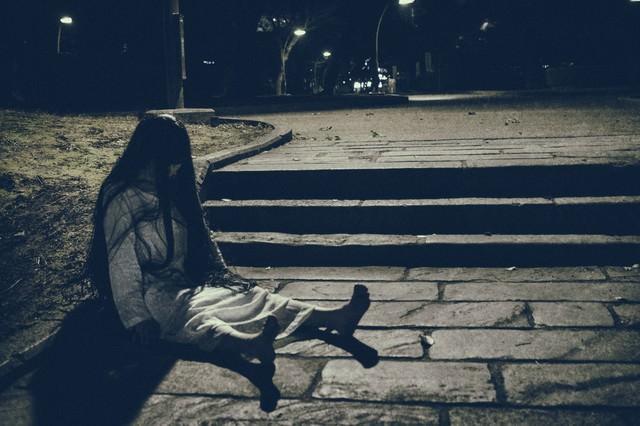 捨てられた人形のように座る女性の姿の写真