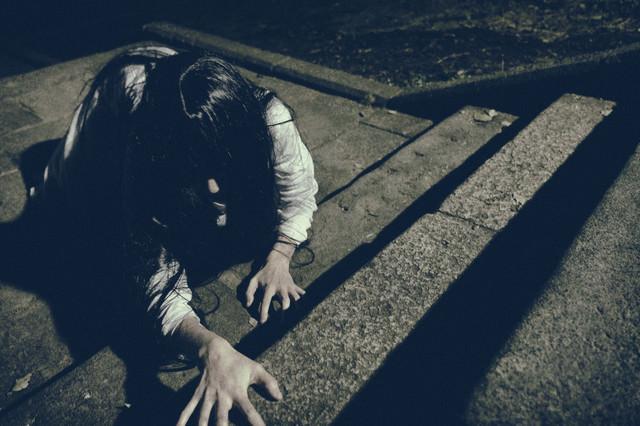 階段を這いつくばる未練を残した女性の写真