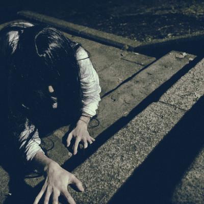 「階段を這いつくばる未練を残した女性」の写真素材