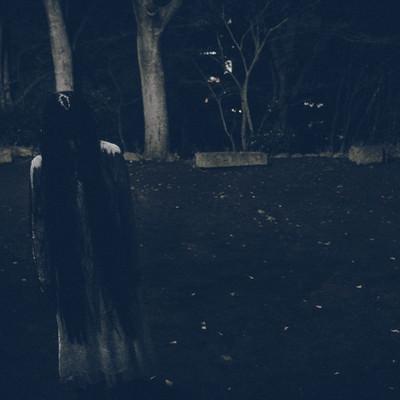 真夜中の広場で項垂れる白いワンピースの女性の写真