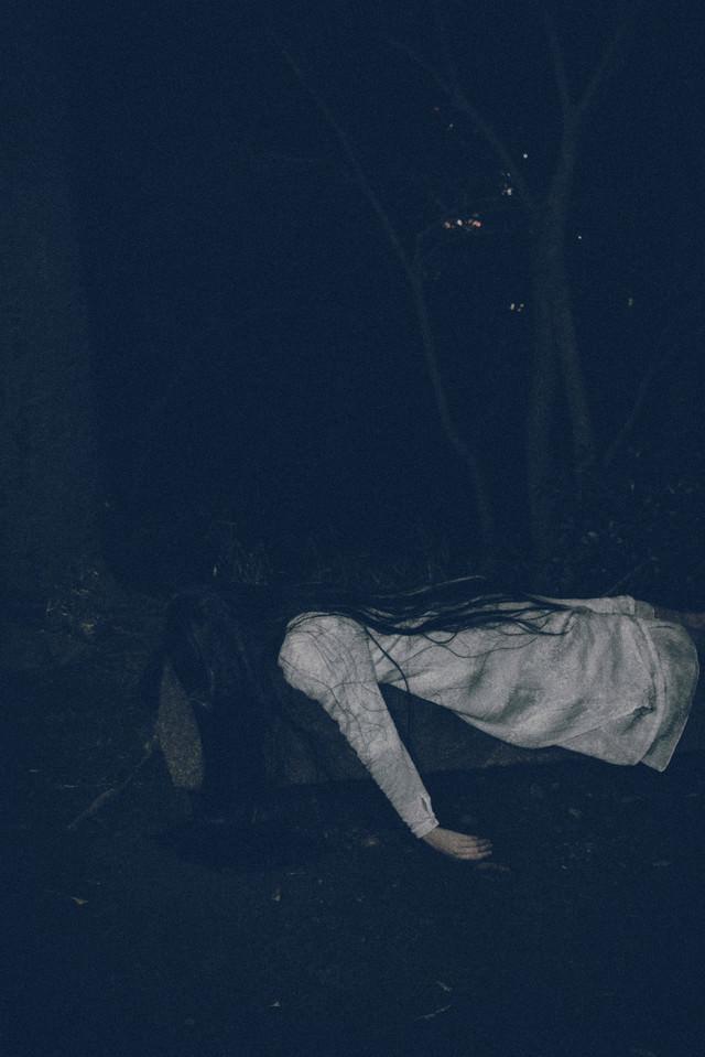汚れた装いでうつ伏せに倒れこむ不気味な女性の写真