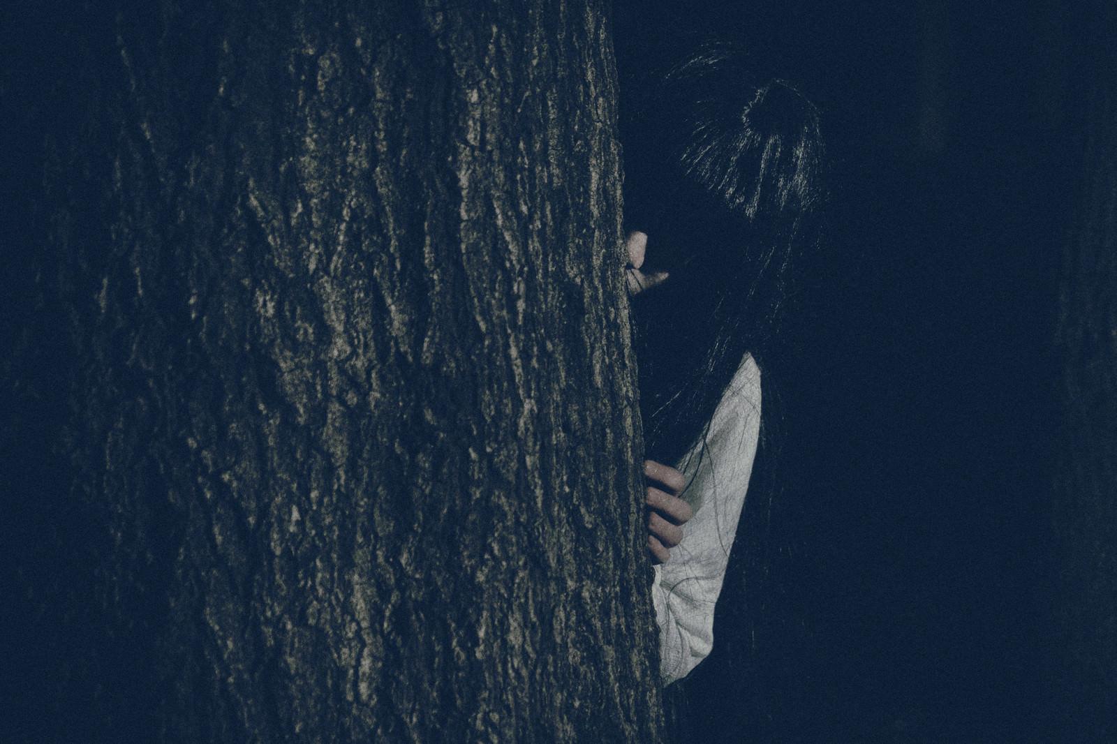 「木の陰からこちらを覗き込む恥ずかしがり屋の貞子さん」の写真[モデル:緋真煉]