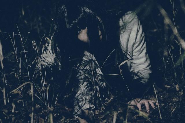 暗闇の中、追い続ける髪の長い女性の写真