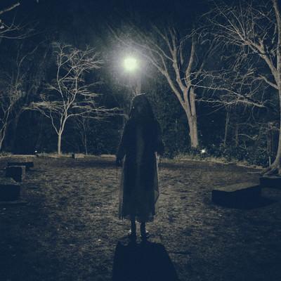 「真夜中の雑木林の中で仁王立ちする女性」の写真素材