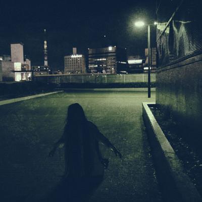 建物の物陰で膝から崩れ落ちる女性の写真