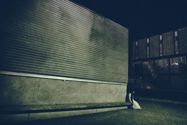 暗い壁沿いに人が座ってるの写真