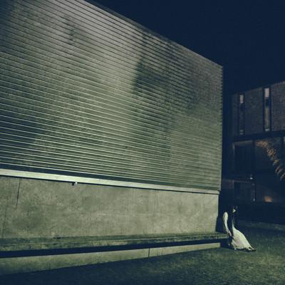 「暗い壁沿いに人が座ってる」の写真素材