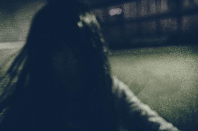 暗がりの中で髪を振り乱す女性の写真