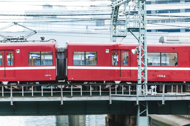 陸橋を走り抜ける電車の側面(京急逗子線)の写真