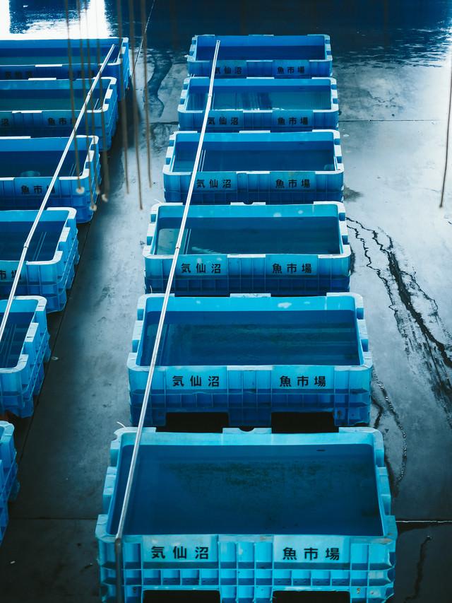 漁港に並ぶ空の水槽の写真