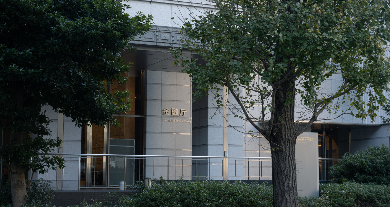 「街路樹と金融庁ビル入口」の写真