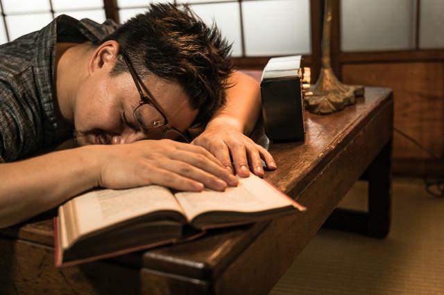 書斎で疲れて寝落ちする男性の写真