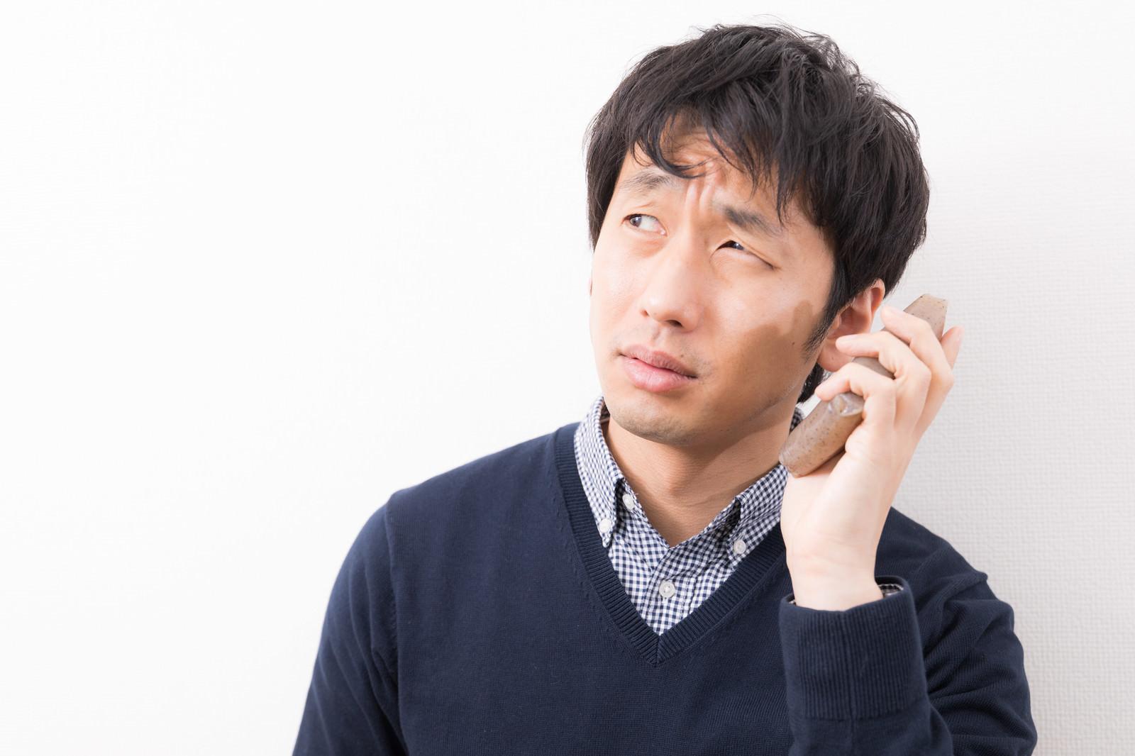 「こんにゃくPhoneを使用する男性」の写真[モデル:大川竜弥]