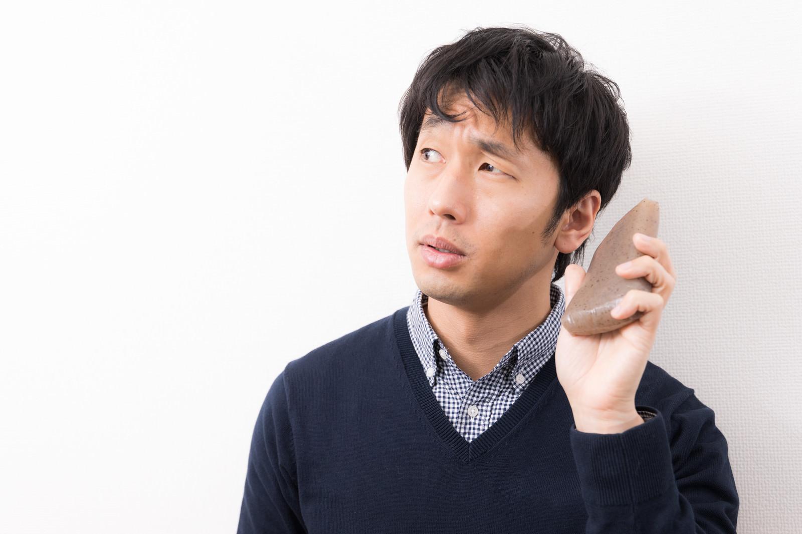 「こんにゃくの音を聞く男性」の写真[モデル:大川竜弥]