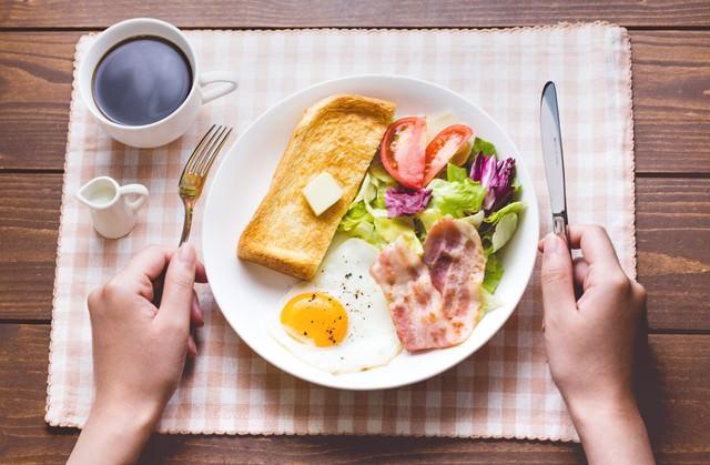 朝食はコーヒーとパン、目玉焼きにベーコンの写真