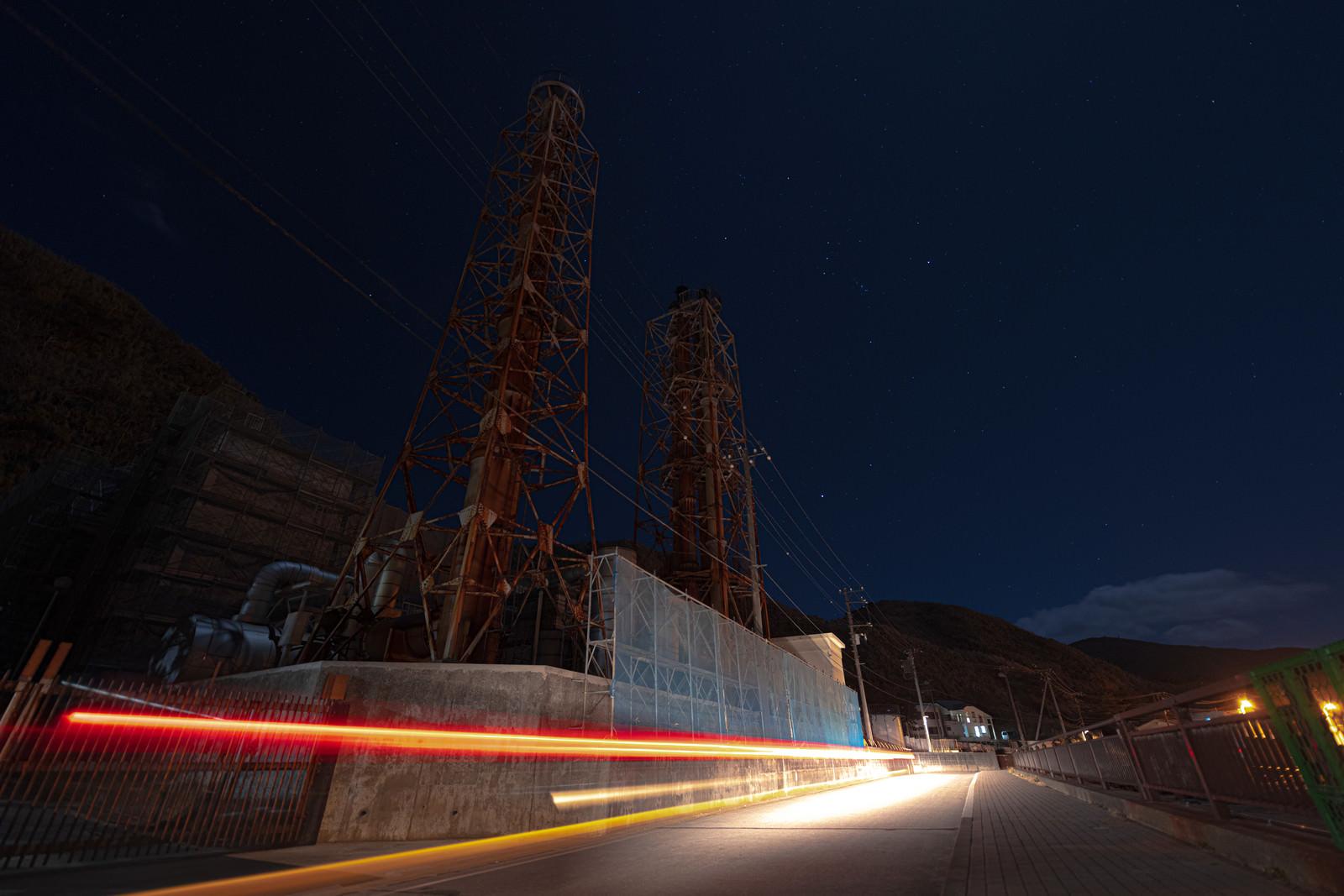 神津本道を走る車の光跡と工場夜景のフリー素材