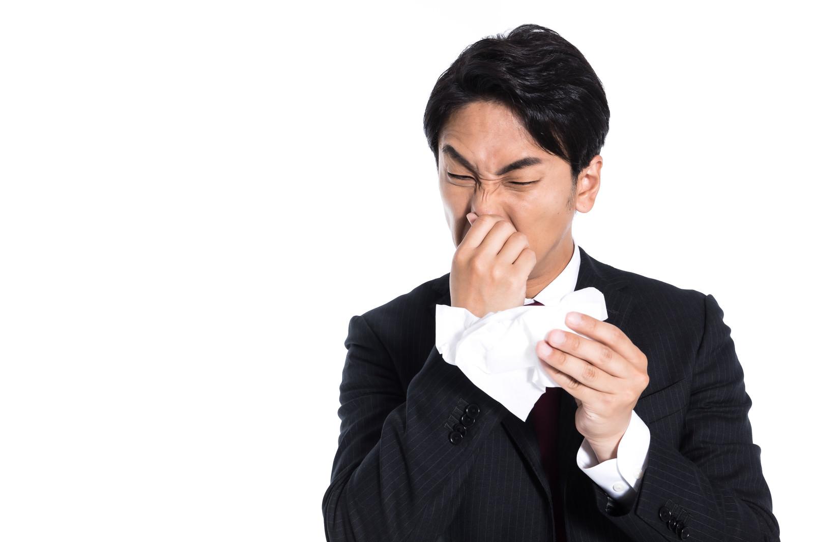 「鼻をかむ(都会の空気の汚さに顔を歪める)」の写真[モデル:大川竜弥]