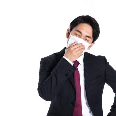 マスク着用で出社しても気分が優れない会社員の写真