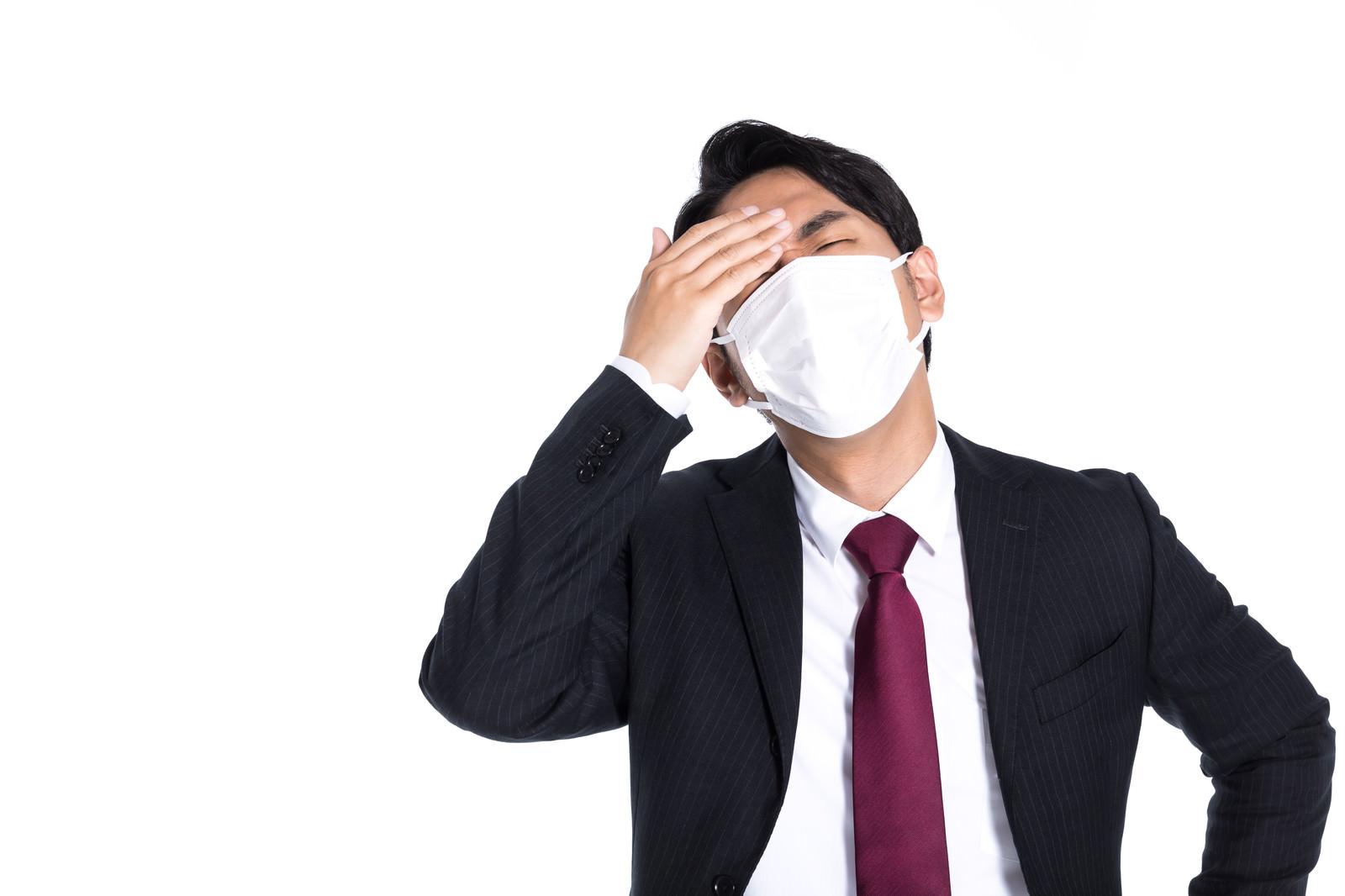「今日も頭痛で体調が悪い風に装うサボり社員」の写真[モデル:大川竜弥]