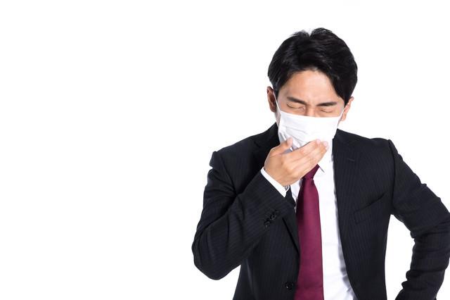 マスク越しに咳き込む会社員の写真