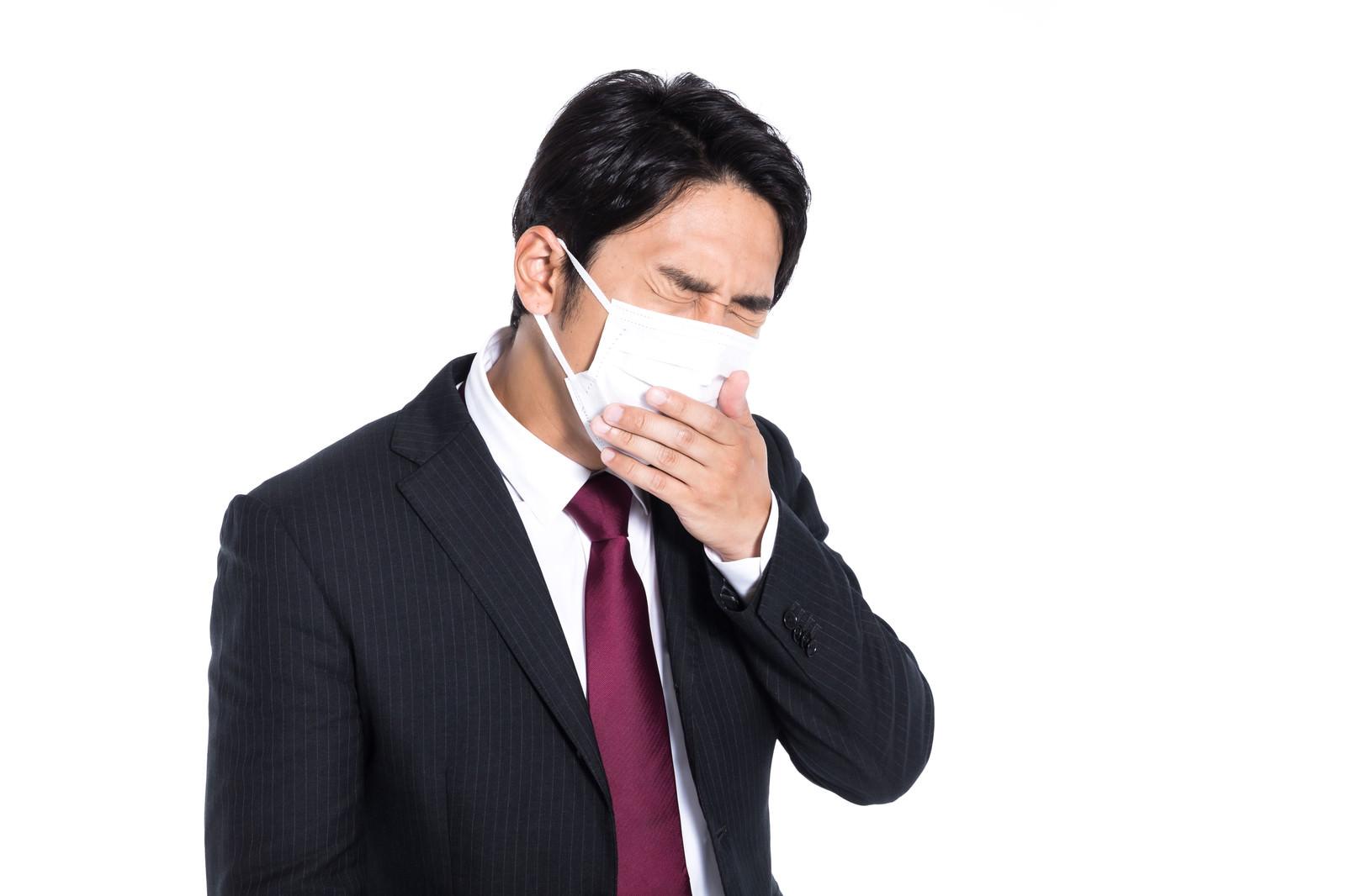 「マスク着用しながら咳が止まらない会社員」の写真