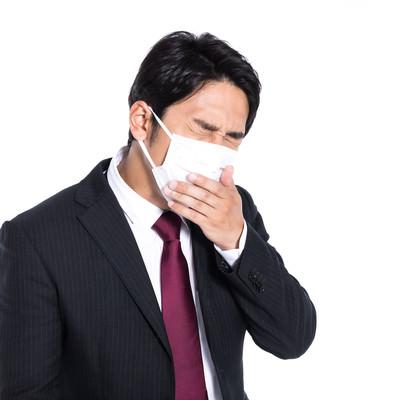 マスク着用しながら咳が止まらない会社員の写真