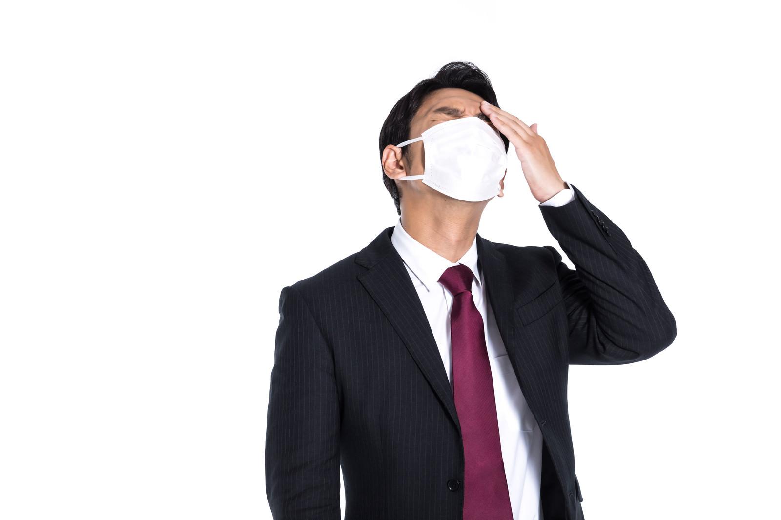 「咳は出るし頭も痛くなってきた会社員」の写真[モデル:大川竜弥]