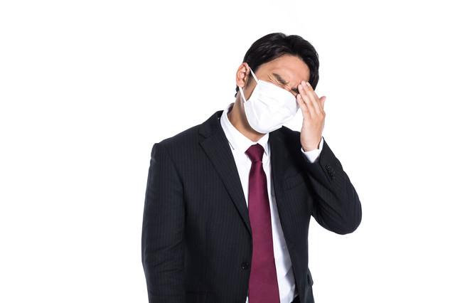 微熱があるのでマスクを着用した会社員の写真