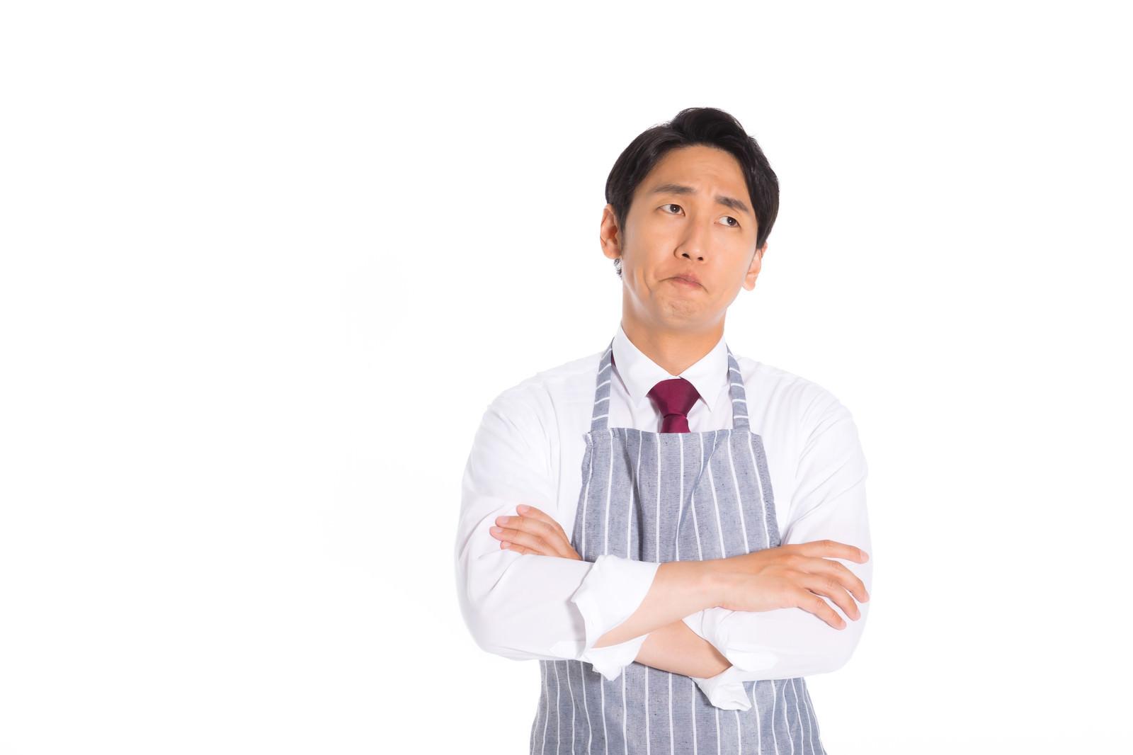「エプロンを着用して考え込む営業マン」の写真[モデル:大川竜弥]