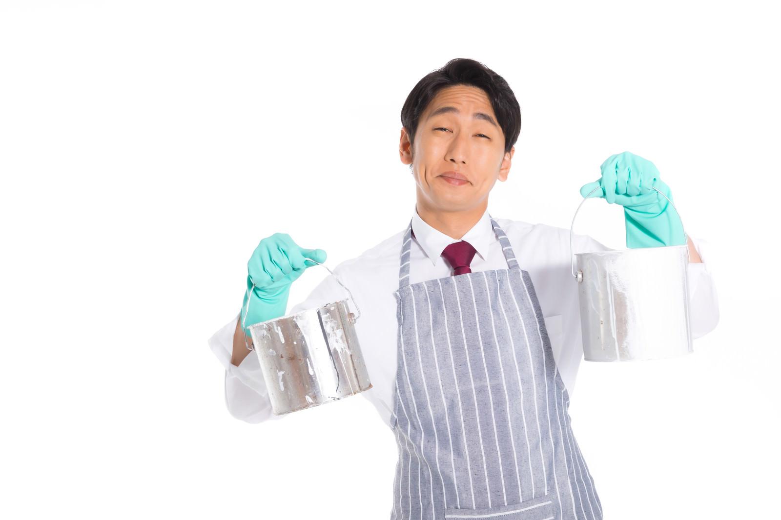 「ペンキ缶を両手で持つエプロン姿の営業マン」の写真[モデル:大川竜弥]