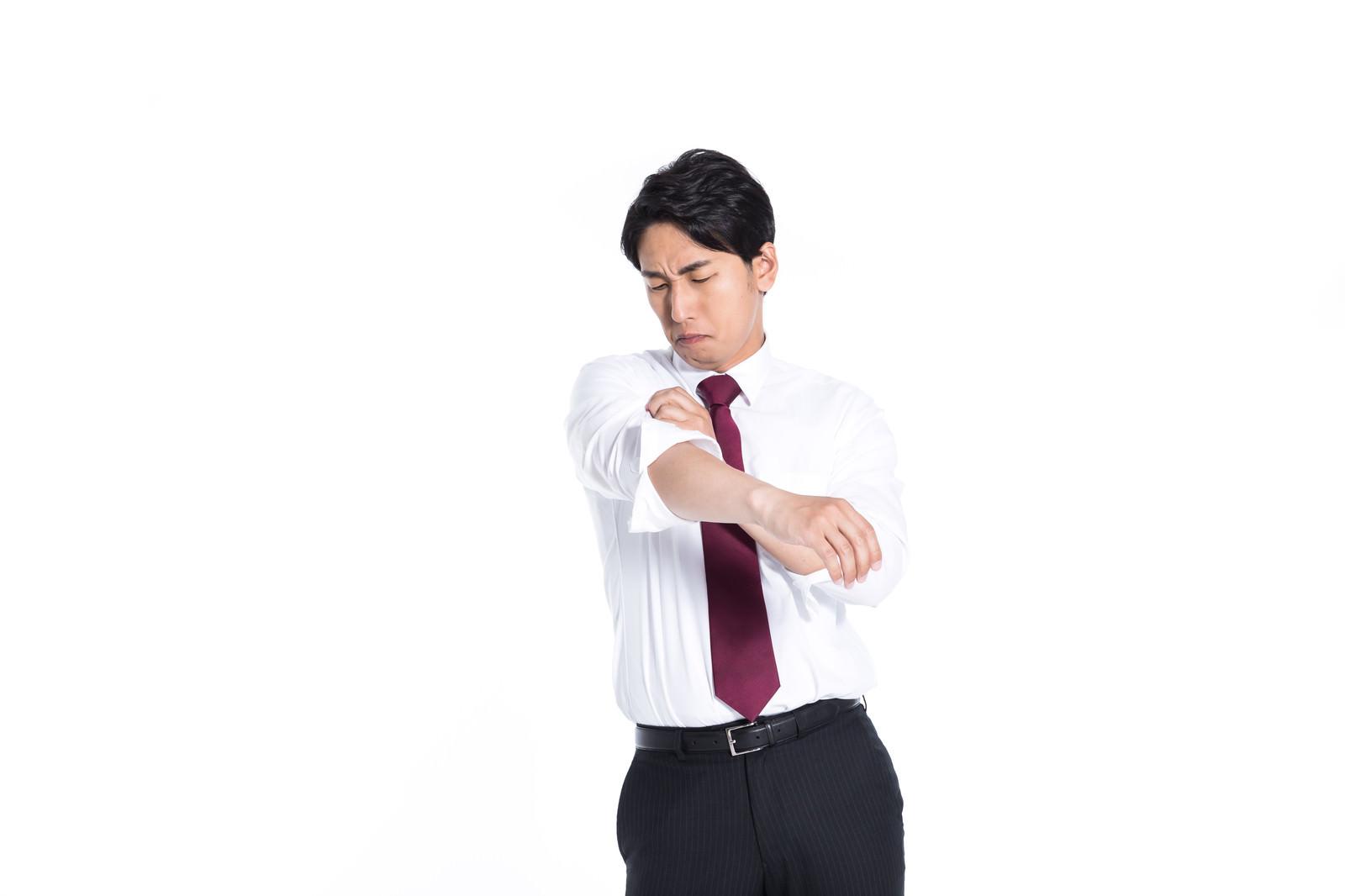 「腕まくりしながらさりげなく脇の臭いをチェックする会社員」の写真[モデル:大川竜弥]