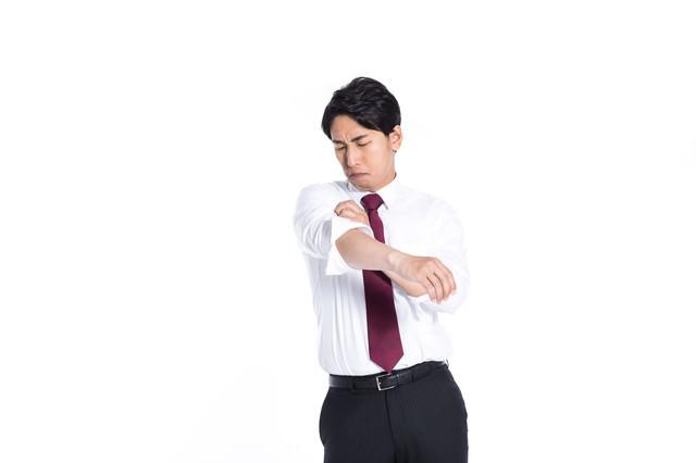 腕まくりしながらさりげなく脇の臭いをチェックする会社員の写真