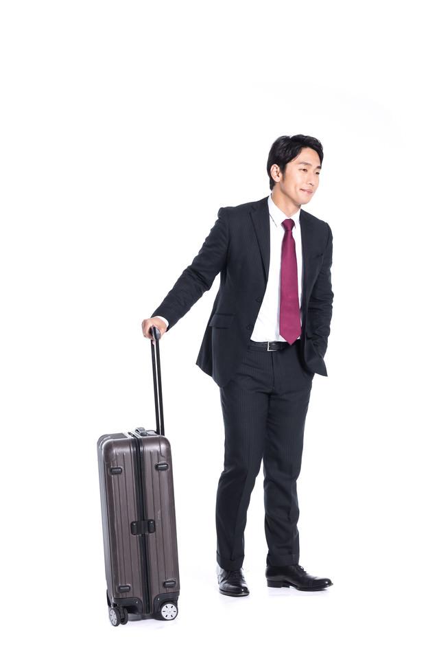 スーツケース片手に出張する会社員の写真