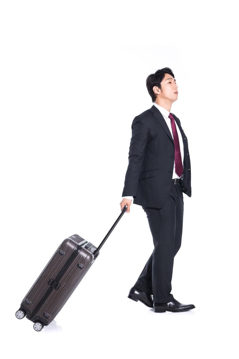 「スーツケースを引きずるビジネスマン」の写真[モデル:大川竜弥]