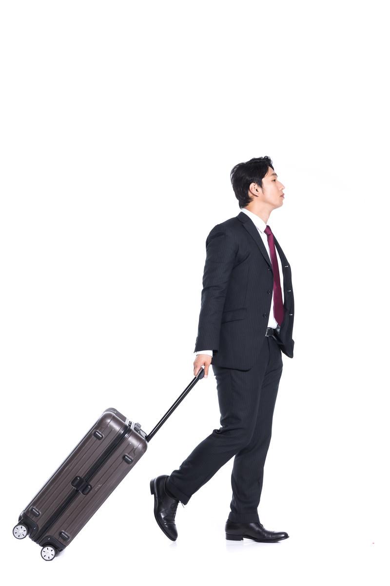 「キャリーバッグをゴロゴロ引いて歩く会社員」の写真[モデル:大川竜弥]