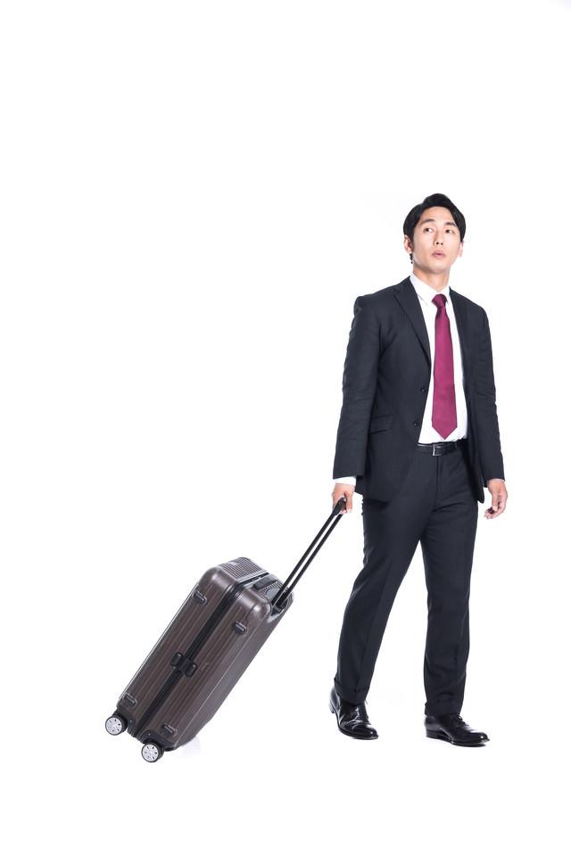 打ち合わせにスーツケース持参する会社員の写真