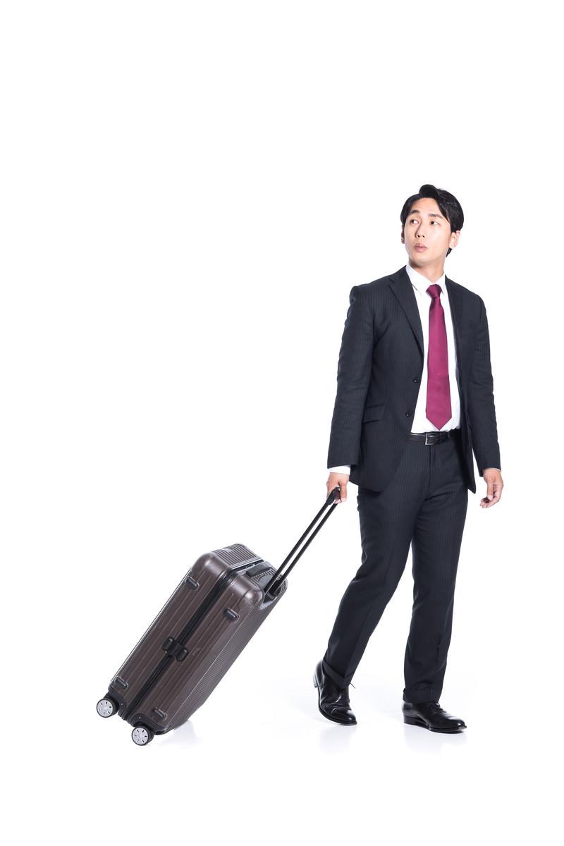 「出張の待ち合わせ場所で同僚を探す男性」の写真[モデル:大川竜弥]