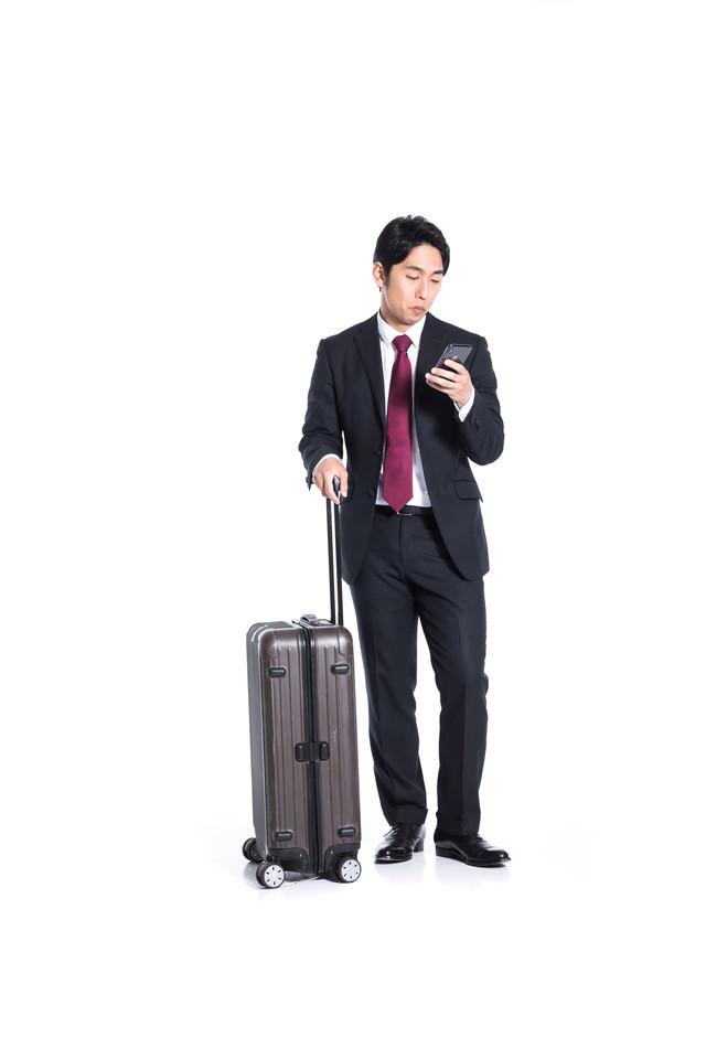 スマートフォンで出張のスケジュールを確認する会社員の写真