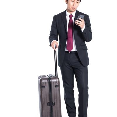 スーツケースを持ってチェックイン時間を確認する会社員の写真